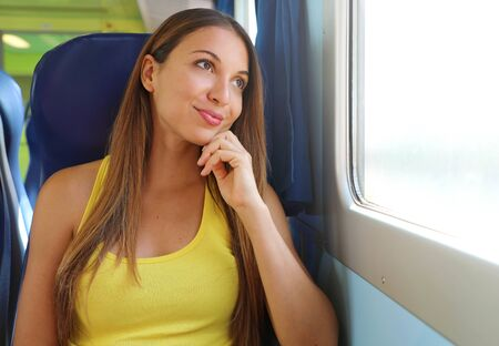 Attractive young woman looking through the train or bus window. Happy train passenger traveling sitting in a seat and looking through the window. 版權商用圖片 - 130794425