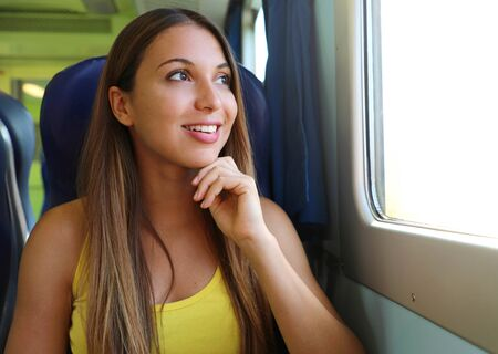 Attractive young woman looking through the train or bus window. Happy train passenger traveling sitting in a seat and looking through the window.
