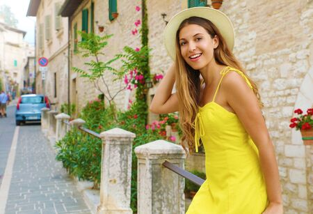 Portrait of young smiling tourist woman in long dress and straw hat in old Europe town.