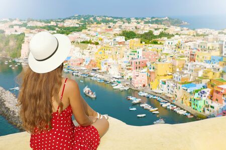 Beautiful young female model with hat in Procida Island with Marina di Corricella harbor and the village on the background, Procida, Italy.