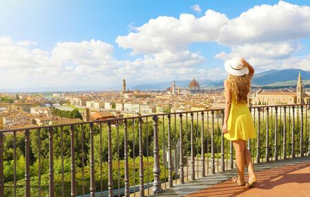 Woman in yellow dress looks at stunning panoramic view of Florence, Italy. Full length of happy cheerful pretty girl in Tuscany.