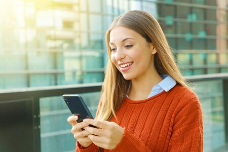 Young business woman wearing orange sweater texting on the smart phone out of the office in a sunny day. Stock fotó