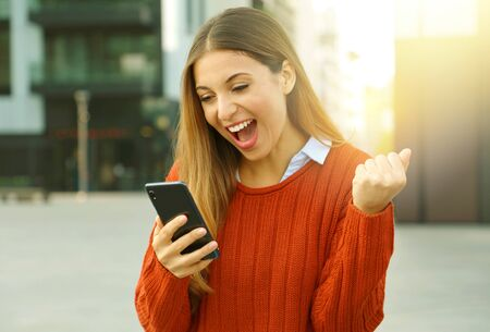 Portrait of an excited woman wearing a red sweater winning online outside on the street in autumn.