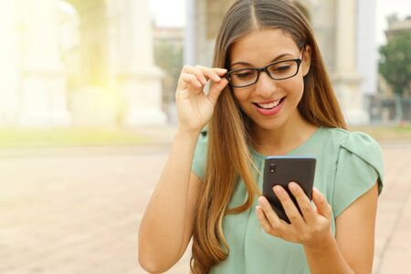 Attractive young business woman reading message on smart phone outdoor. Copy space. Фото со стока