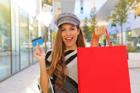 Happy smiling fashion woman holding shopping bag and credit card in her hands in a mall.