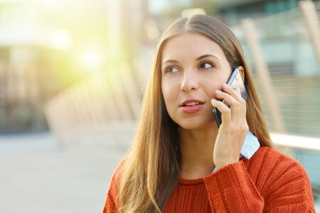 Close up of woman talking on the phone taking a conversation in autumn on modern street background.