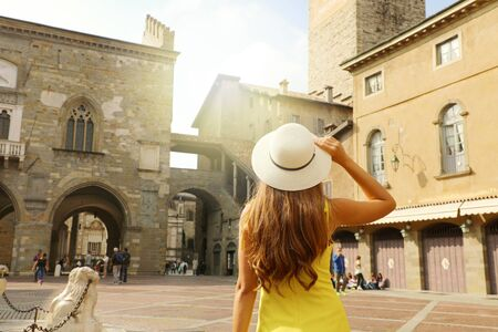 Beautiful girl with hat visiting Piazza Vecchia square in Bergamo Citta Alta medieval old city of Lombardy region in Italy. Фото со стока
