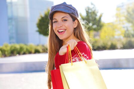 Happy cheerful christmas woman holding shopping bags outdoors. Stock Photo