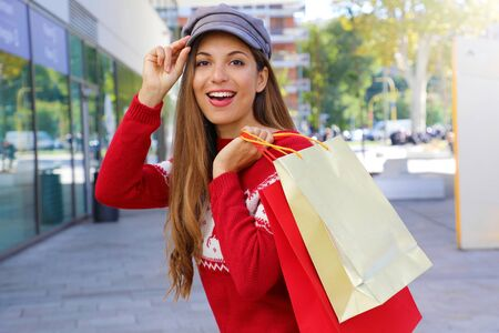 Fashion shopper christmas woman in the street holding shopping bags. Stock Photo