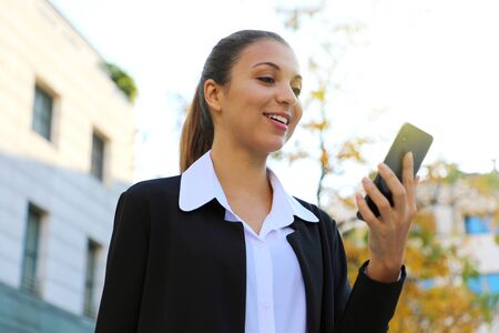 Portrait of cheerful young business woman reading good news on smart phone outdoor. 版權商用圖片
