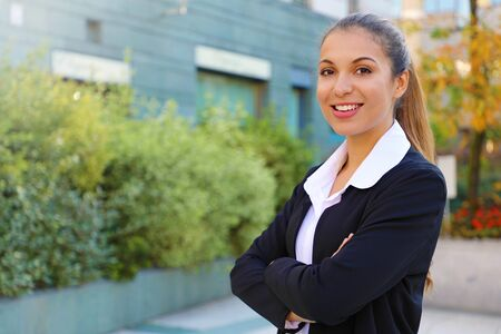 Smiling confident business woman looks at camera with crossed arms outdoor.