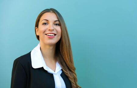 Smiling young business woman with suit standing against blue background outdoor. Copy space.