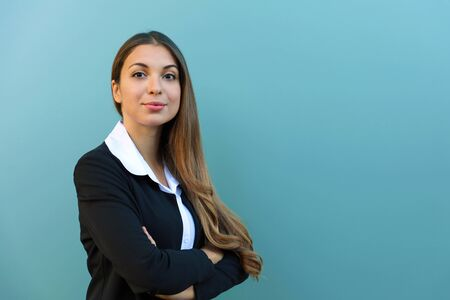 Confident business woman with suit standing against blue background with crossed arms outdoor. Copy space. Фото со стока