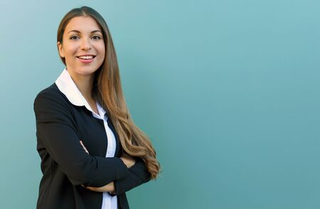 Smiling business woman with suit standing against blue background with crossed arms outdoor. Copy space. Фото со стока