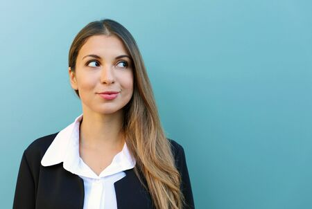 Portrait of business woman standing against blue background looking to the side. Copy space.