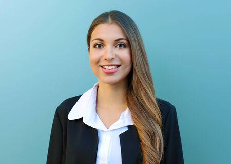 Giovane donna d'affari con tuta in piedi su sfondo blu all'aperto. Archivio Fotografico