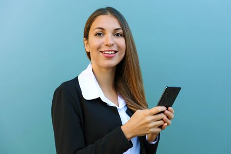 Young business woman holding mobile phone looking at camera against blue background outdoors.