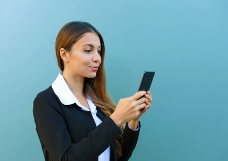 Portrait of beautiful young business woman chatting with smart phone outdoors. Фото со стока
