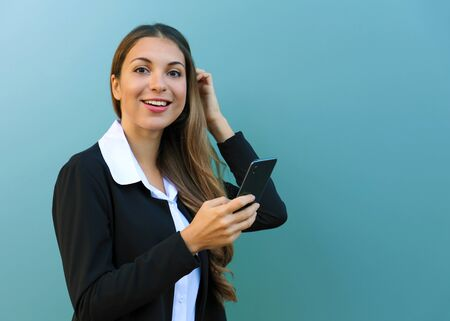 Young business woman holding mobile phone looking at camera against blue background outdoors. Copy space. Фото со стока