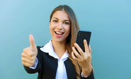 Happy cheerful business woman showing thumb up after reading good news on mobile phone outdoors.