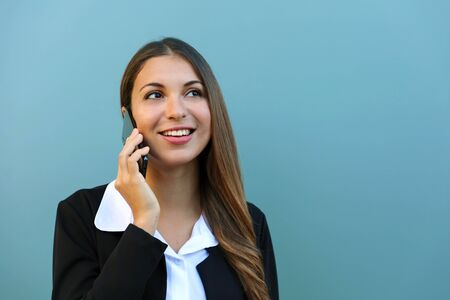 Businesswoman talking on mobile phone with client outdoor against blue background. Copy space.