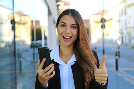 Pretty beautiful young business woman holding smart phone gives thumb up in the street. Фото со стока