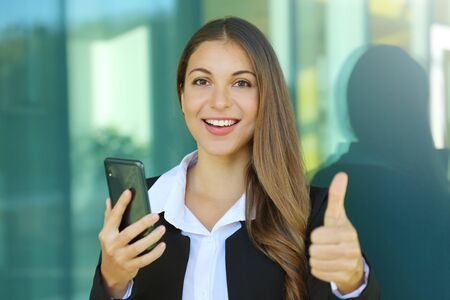 Business woman using mobile phone shows thumb up outdoors.