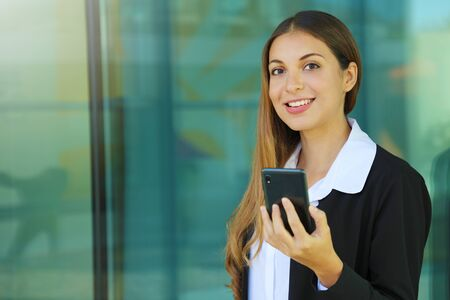 Business woman holding mobile phone and looking at camera outdoors. Copy space.