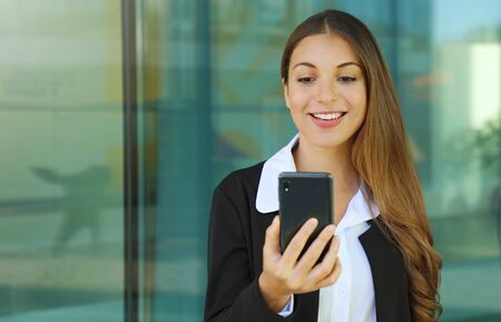 Business woman checking her smart phone out of office.
