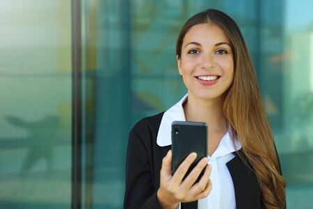 Happy young business woman checking her smart phone and looking at camera out of office. Copy space.