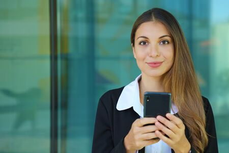 Young business woman checking her smart phone and looking at camera out of office. Copy space. Фото со стока