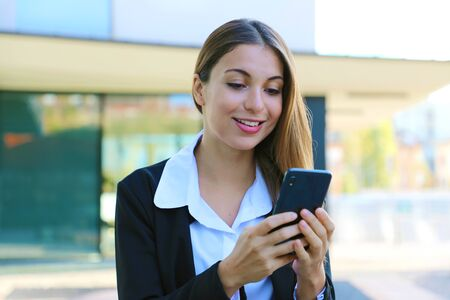 Close up of young business woman typing with smart phone outdoors.