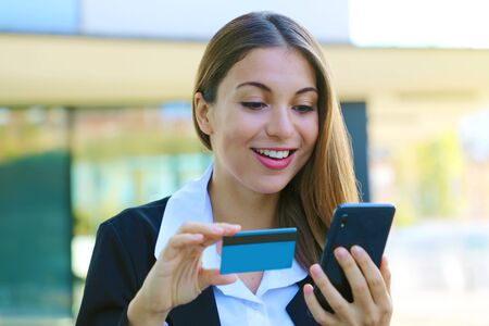 Beautiful business woman holds smart phone and credit card making shopping online outdoor office on break time. People and online payment concept.