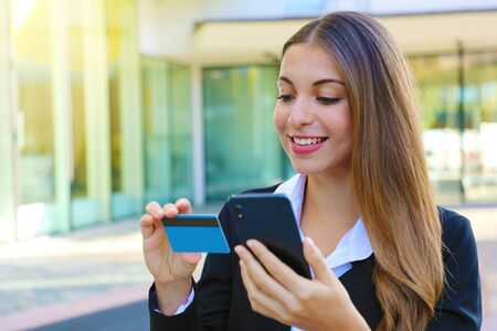 Business woman holding smart phone reading credit card number making shopping online outdoor office on break time. People and online payment everywhere concept.