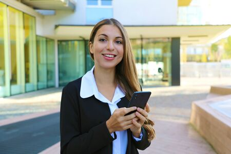 Young business woman using smart phone outdoor looking at camera.