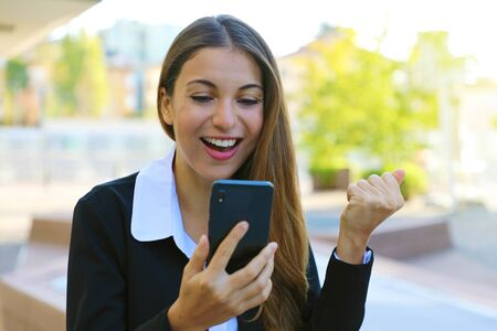 Happy successful business woman reading good news on smartphone and celebrate outdoor.