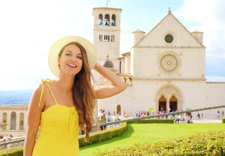 Happy smiling beautiful girl in Assisi, Italy. Young woman visiting the Basilica of Saint Francis of Assisi on sunny day.