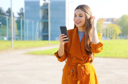 Portrait of attractive young woman walking outside and reading text message on mobile phone.