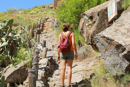 Tourist girl backpacker reading map on the tourist path in Tenerife, Canary Islands, Spain. Фото со стока