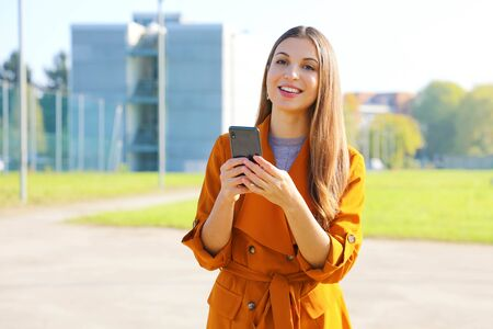 Smiling beautiful business woman in casual clothes using smart phone outdoors and looking at camera. Фото со стока