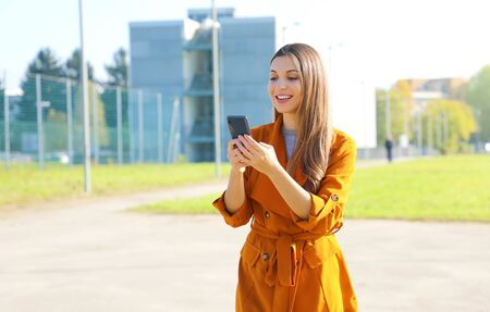 Pretty young woman typing message with her smart phone app outdoor.