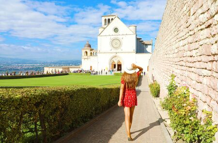 Tourism in Italy. Back view of beautiful girl with red dress walking towards the Basilica of Saint Francis of Assisi in Umbria, Italy.
