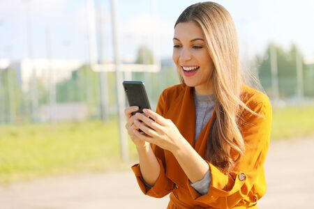 Happy beautiful woman walking and writing or reading sms messages online on a smart phone.
