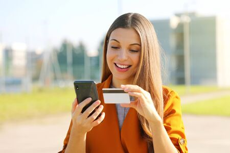 Close up of pretty woman reading credit card number doing online payment with her mobile phone outside.