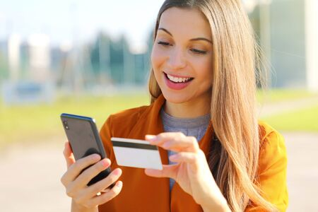 Close up of beautiful woman reading credit card number making online payment on her mobile phone outside on a sunny autumn day. Фото со стока