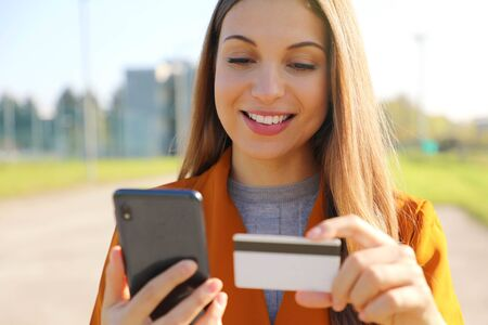 Close up of beautiful woman reading credit card number doing online payment on her smart phone outside on a sunny autumn day.