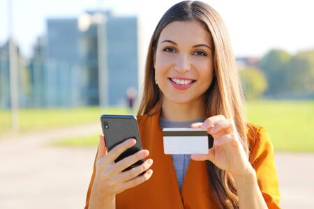 Close up of beautiful woman looking at you holding credit card doing online payment on her smart phone outside on sunny autumn day. Фото со стока