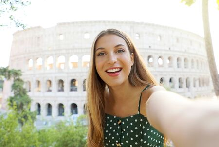 Young woman take self portrait with behind the Colosseum in Rome, Italy.