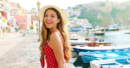 Portrait of beautiful fashion girl in Procida, Italy. Attractive young woman with red dress and hat walks along the harbor of Procida Island in Italy. Фото со стока