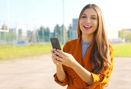 Portrait of happy business woman looking at camera holding smart phone outdoor. Фото со стока